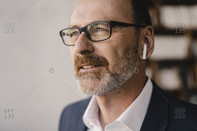 Portrait of mature businessman listening to music with bluetooth earbuds