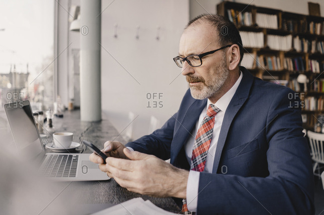 Mature businessman using cell phone and laptop in a cafe