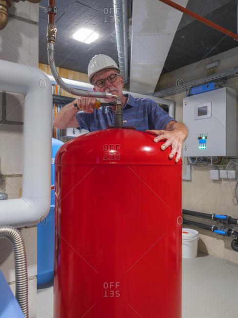 Senior craftsman checking water-processing unit