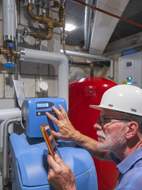 Senior craftsman checking water-processing unit- reading tablet