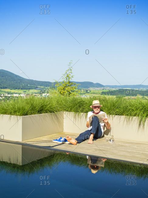 Senior man reading newspaper at swimming pool