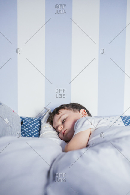 Little boy sleeping on bed in the morning