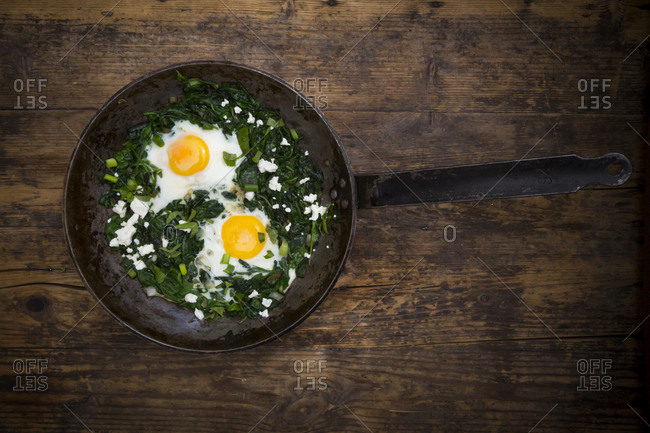 Green Shakshouka with baby spinach- chard- spring onions and basil in a pan