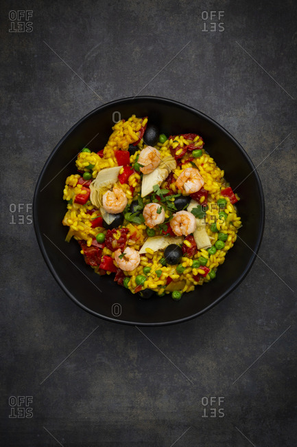 Paella with rice- bell pepper- tomato- artichoke- pea- black olive- curcuma and shrimps