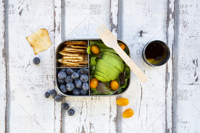 Lunchbox with salad- avocado and yellow tomato- cracker- blueberry and salad dressing- from above
