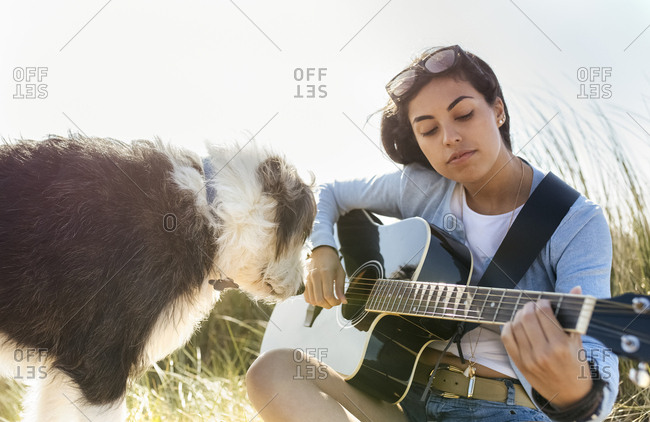 Young woman with dog playing guitar on the beach