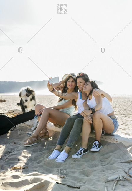 Happy female friends with dog taking a selfie on the beach