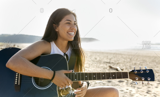 Happy young woman with guitar on the beach