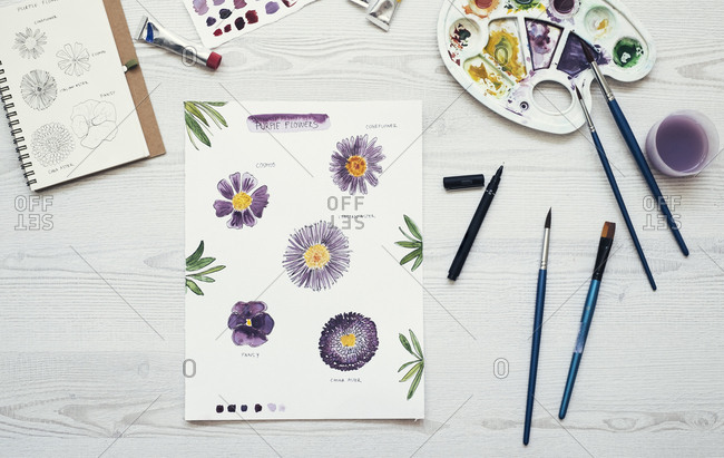 Watercolor painting of purple flowers on the desk- top view
