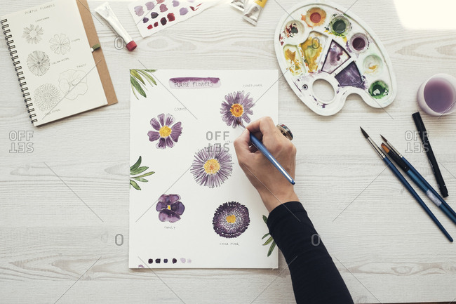 Woman painting flowers with water colors- top view