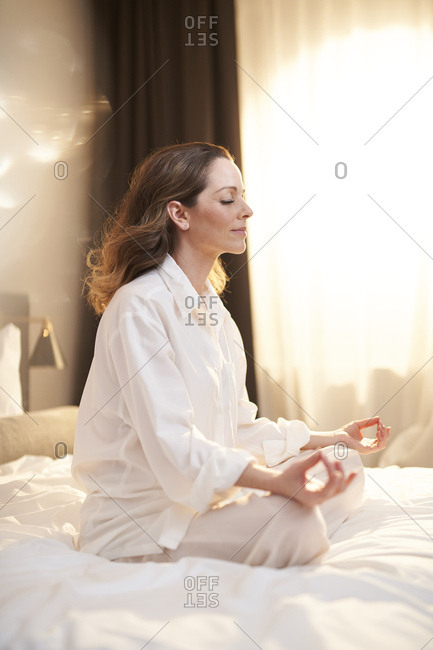 Woman sitting on bed in yoga pose