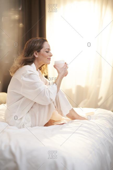 Brunette woman sitting on bed holding cream jar