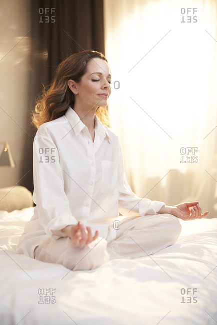 Woman sitting on bed - Offset
