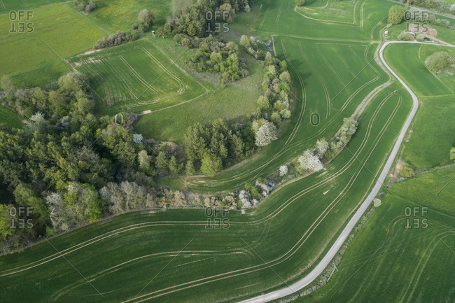 Aerial view of rural road through landscape with meadow- trees- and agricultural fields- springtime- Franconia- Bavaria- Germany