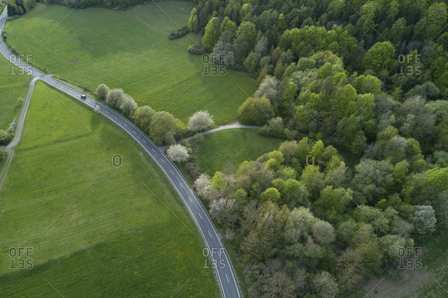 Abstract aerial view of rural road through landscape with agricultural fields- meadows and forest- springtime- Franconia- Bavaria- Germany