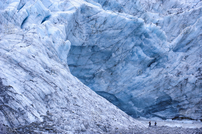 Tourists hiking to the giant glacial outflow of Fox Glacier- South Island- New Zealand