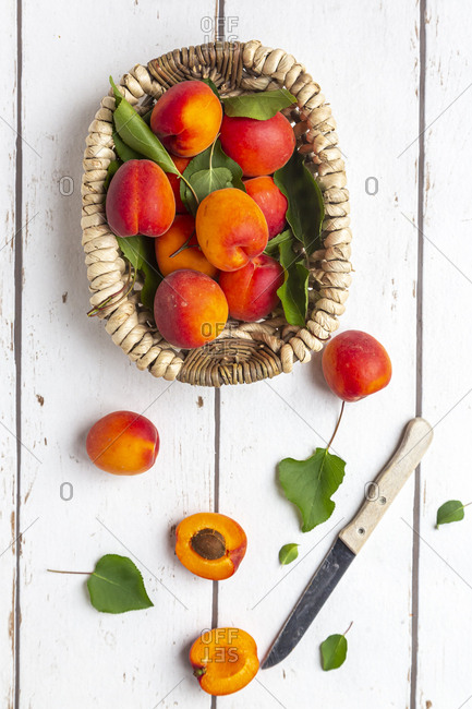 Apricots in basket- knife on white wood