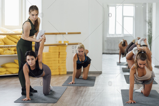 Fitness instructor practicing with young women in gym