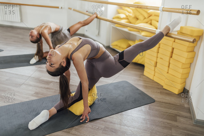 Two young women doing barre workout in gym