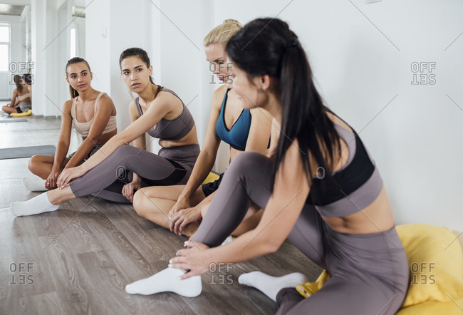 Young women having a break from workout in gym