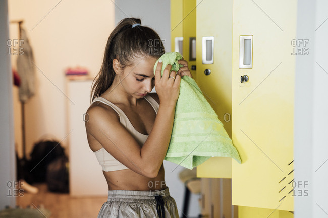 Young woman in locker room finishing workout in gym