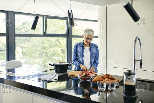 Senior woman standing in kitchen- chopping strawberries