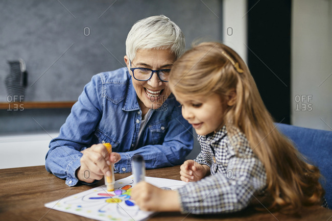 Grandmother and granddaughter sitting at table- painting coloring book