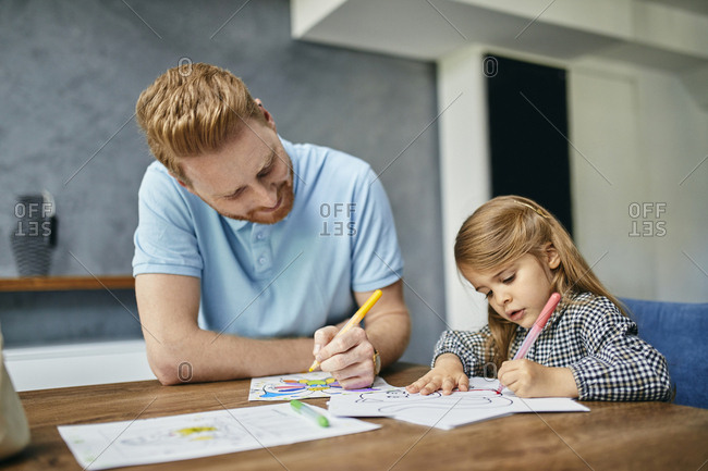 Father and daughter sitting at table- painting coloring book