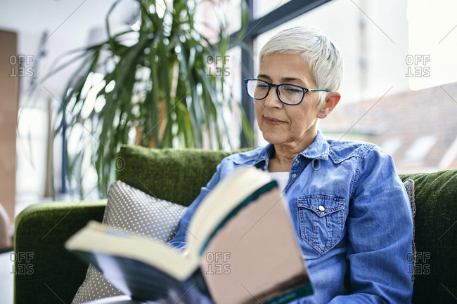 Senior woman sitting on couch- reading a book
