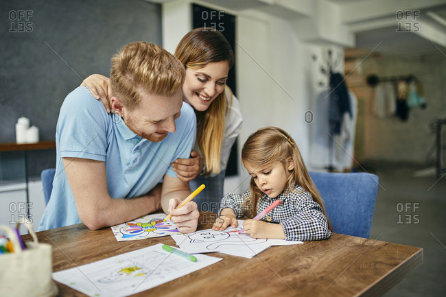 Mother and father watching daughter- painting coloring book