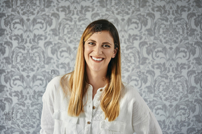 Portrait of a happy- blond woman in front of patterned wallpaper