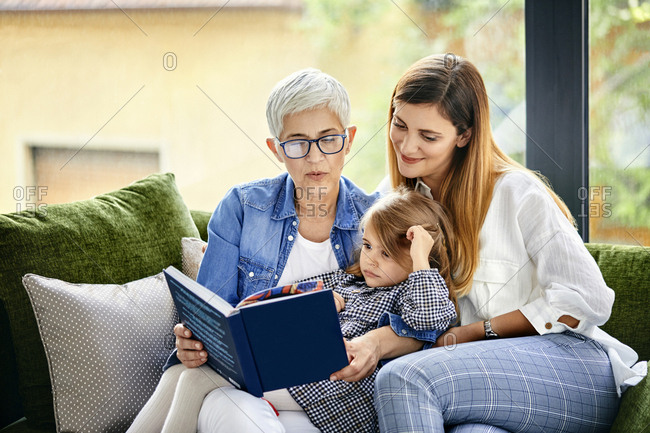 Mother- daughter and granddaughter sitting on couch- reading a book