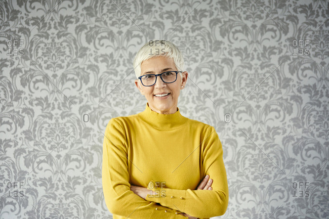 Portrait of a senior woman against a patterned wallpaper