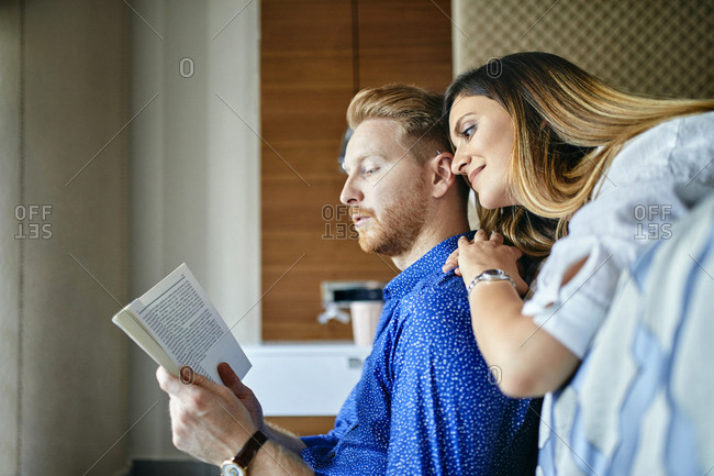 Affectionate couple reading book together in bedroom