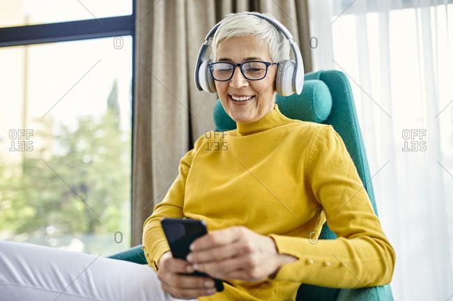 Senior woman with headphones using smartphone