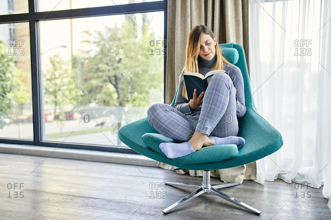Woman sitting in armchair- reading book