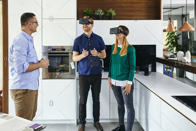 Couple wearing VR glasses shopping for a new kitchen in showroom