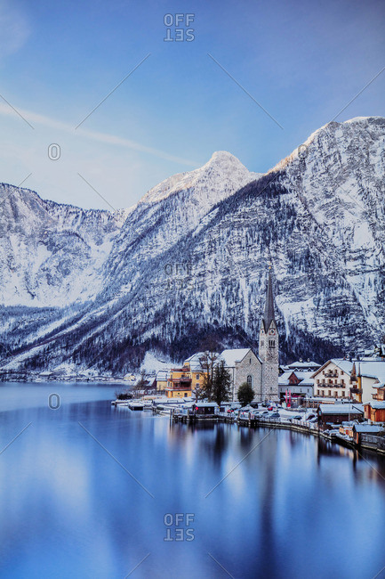 Austria - February 7, 2019: Typical village called Hallstatt con the Hallstatter see at sunrise with the houses reflecting in the lake
