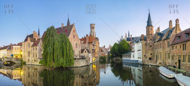 Belgium - August 17, 2016: Belgium, West Flanders (Vlaanderen), Bruges (Brugge). Belfort van Brugge and medieval buildings on the Dijver canal from Rozenhoedkaai at dawn.