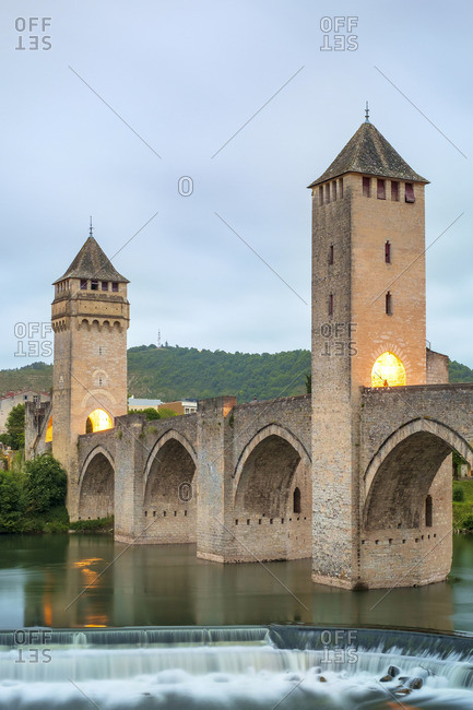 Medieval Pont Valente bridge over the Lot River at dawn on cloudy morning, Cahors, Lot Department, Midi-Pyrenes, France
