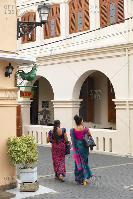 Sri Lanka - April 26, 2019: Women walking past The Fort Printers Hotel, Galle, Southern Province, Sri Lanka