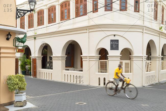 Sri Lanka - April 26, 2019: Man cycling past The Fort Printers Hotel, Galle, Southern Province, Sri Lanka