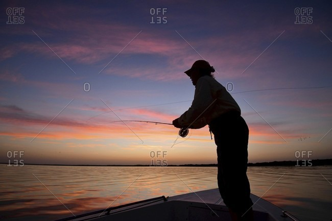 Man fly fishing from motorboat in Campeche, Mexico
