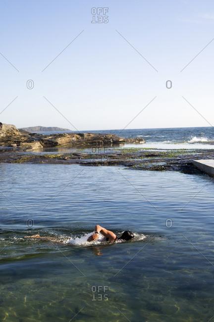 Man swims in ocean rock pool.