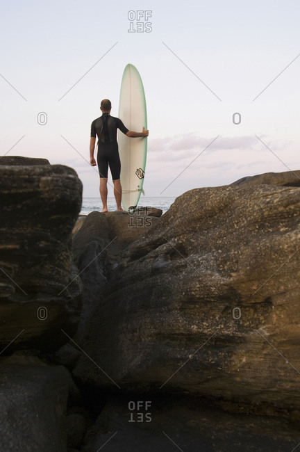 Surfer with board watches ocean.