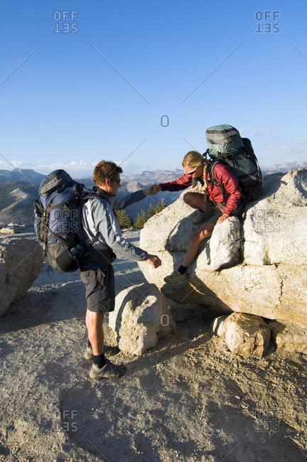 Hiker being helped off of rock.