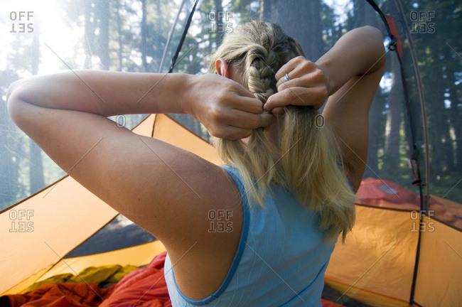 Woman braiding hair in tent.