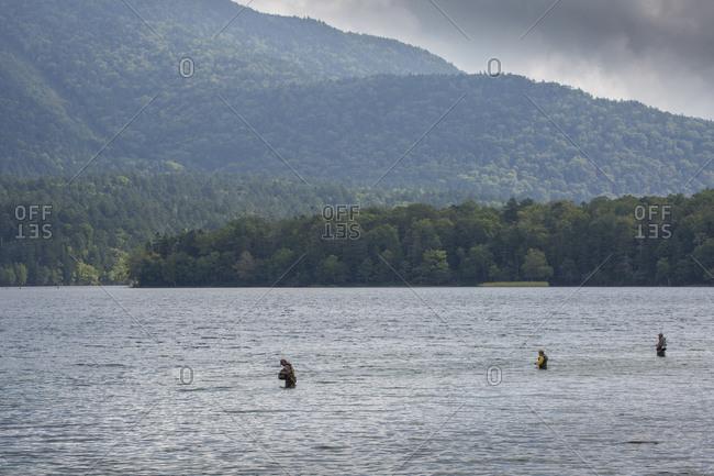 Three fishermen fly-fishing in Lake Akan, Hokkaido, Japan