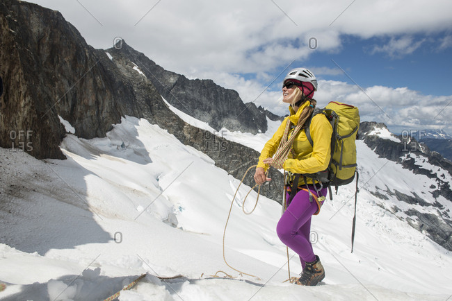 Woman mountaineer coils a rope on a glacier in North Cascades National Park.