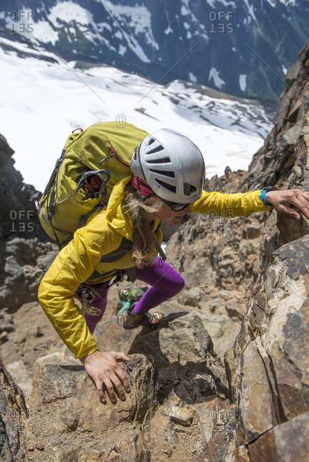 Woman Mountaineer climbing up rock in North Cascades National Park.